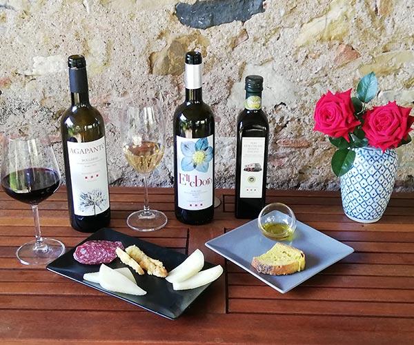 Tavola con prodotti tipici e bottiglie di vino e olio per degustazione